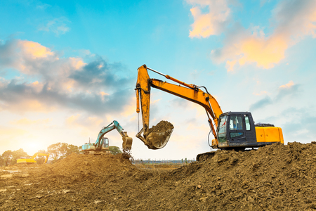 excavator in construction site on sunset sky background Фото со стока