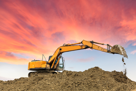 excavator in construction site on sunset sky background Stock Photo