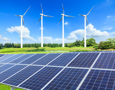 Wind turbines and solar panels on green field Stock Photo