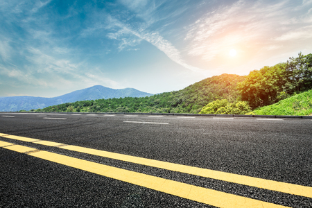 asphalt road and mountain landscape at sunset Stock Photo
