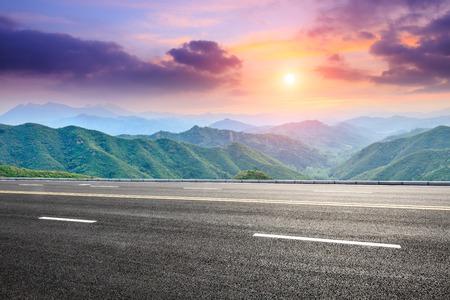 asfaltweg en berglandschap bij zonsondergang
