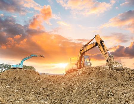 Excavator working at construction site on sunset Standard-Bild