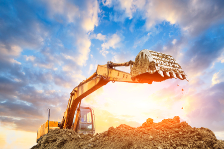 Excavator working at construction site on sunset Stockfoto