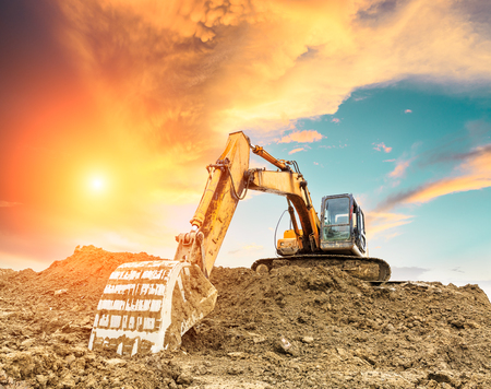Excavator working at construction site on sunset 스톡 콘텐츠
