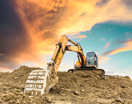 Excavator working at construction site on sunset Archivio Fotografico