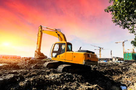 Excavator working at construction site on sunset Stock Photo