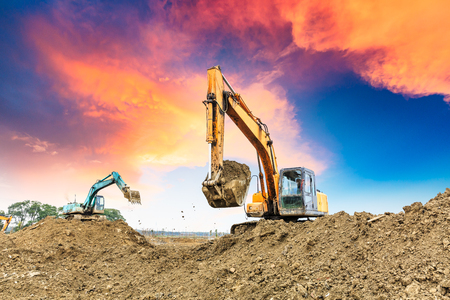 earthmover: Excavator working at construction site on sunset Stock Photo