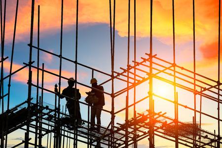 werknemers en bouwplaats bij zonsondergang Stockfoto