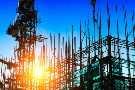 estate: Construction site with crane and workers at sunset Stock Photo