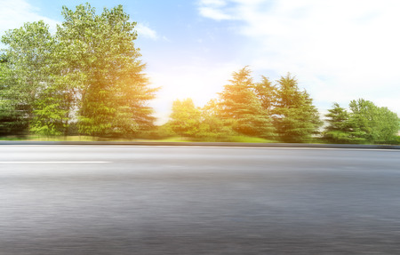 Motion blur asphalt road and forest under the blue sky Stock Photo