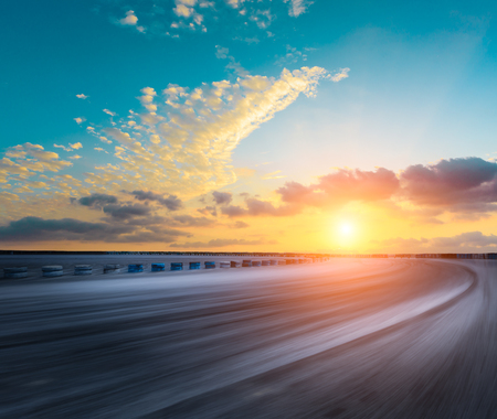 Motion blur asphalt road circuit and beautiful sky clouds at sunset