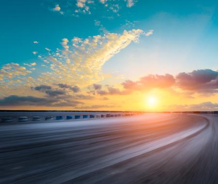 Motion blur asfalt wegcircuit en mooie hemel wolken bij zonsondergang Stockfoto