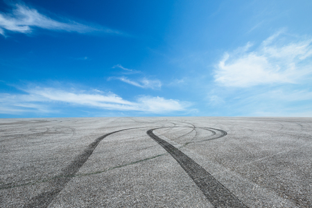 Asphalt road circuit and sky clouds with car tire brake