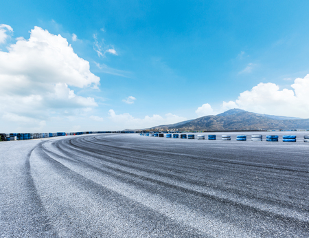Asphalt road circuit and hill under the blue sky