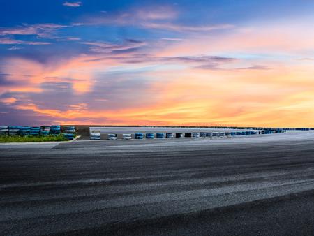 Dark asphalt road circuit and beautiful sky at sunset