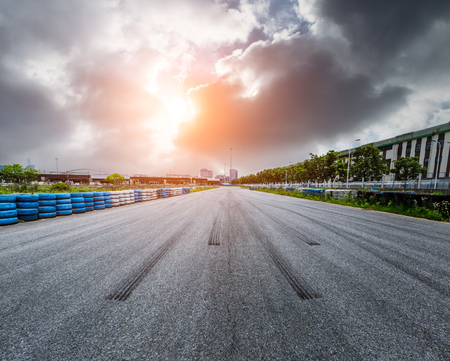 Asphalt road circuit and sky sunset with car tire brake 写真素材