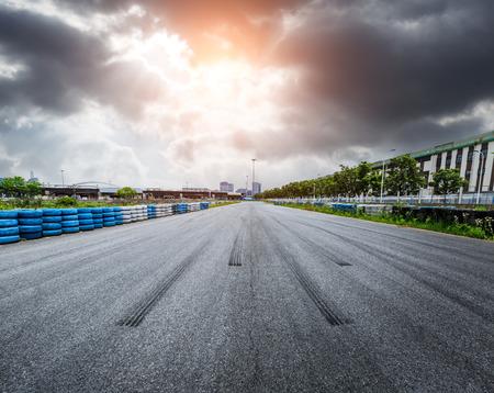 De wegkring van het asfalt en hemelzonsondergang met de rem van de autoband