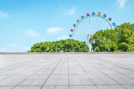 Empty floor square and playground ferris wheel in the city park
