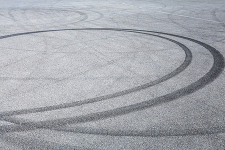 Abstract background black tire tracks skid on asphalt road, high angle shot view in racing circuit