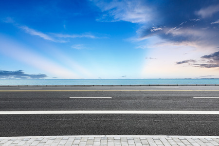 empty asphalt highway and blue sea nature landscape Banco de Imagens