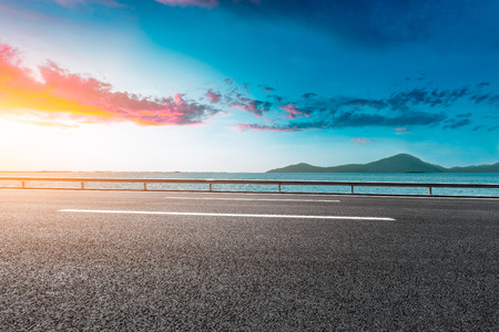 empty asphalt highway and blue sea nature landscape at sunset Banque d'images