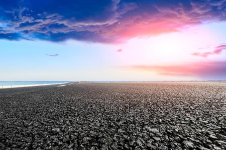 empty asphalt highway and blue sea nature landscape at sunset Stock Photo