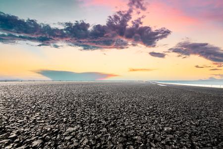 empty asphalt highway and blue sea nature landscape at sunset Standard-Bild