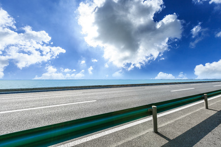 Empty asphalt highway and beautiful sea under the blue sky