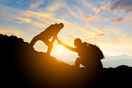 people helping each other hike up a mountain at sunrise,giving a helping hand,concept scene Stockfoto