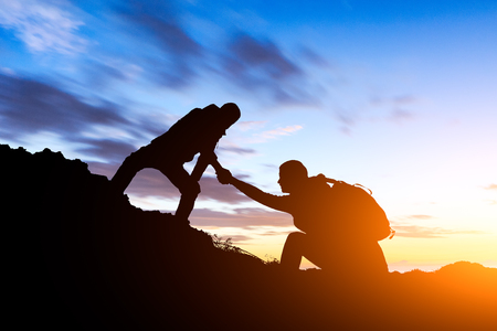 people helping each other hike up a mountain at sunrise,giving a helping hand,concept scene Stock Photo