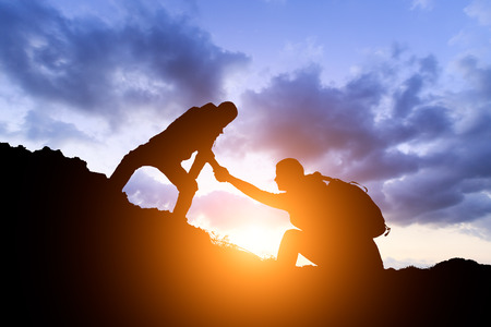 people helping each other hike up a mountain at sunrise,giving a helping hand,concept scene Banque d'images