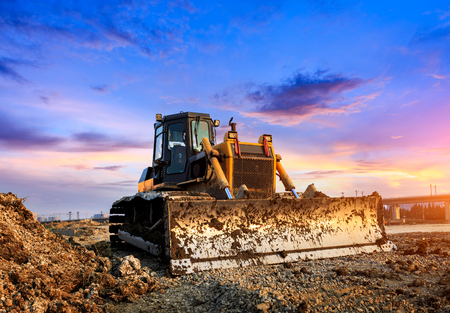bulldozer at construction site and sunrise landscape Imagens