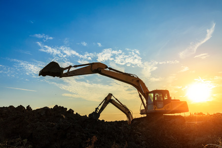 excavator working on construction site and sunrise landscape Stock Photo