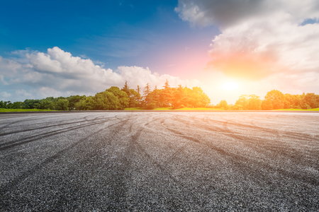 empty asphalt road ground and green forest at sunset