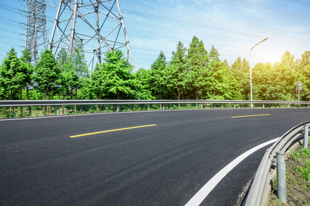 Curved asphalt highway and green forest 스톡 콘텐츠