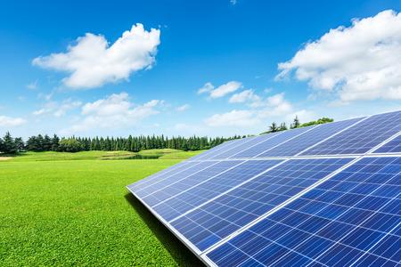 Sonnenkollektoren und grünes Gras unter dem blauen Himmel Standard-Bild