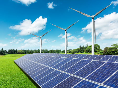 Solar panels and wind turbines in green grass field Stockfoto