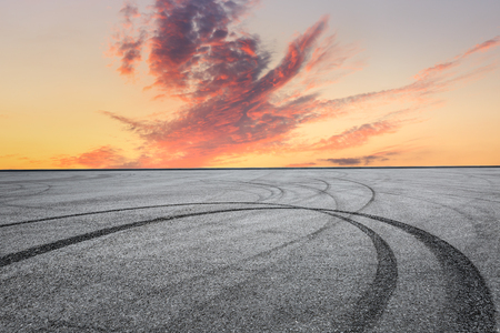 Asphalt square car tire brakes and colorful sky clouds at sunrise 스톡 콘텐츠