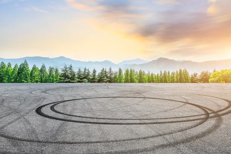 Empty asphalt square and mountain with forest scenery at sunrise 写真素材