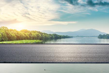 Asphaltstraße und schöner Berg mit See bei Sonnenuntergang