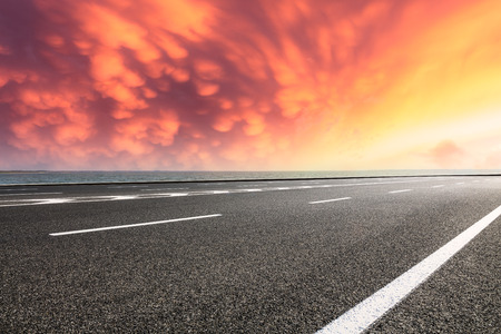 Asphalt road and dramatic sky with coastline at sunset Stock Photo