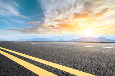 Asphalt road and mountains at sunset Stock Photo