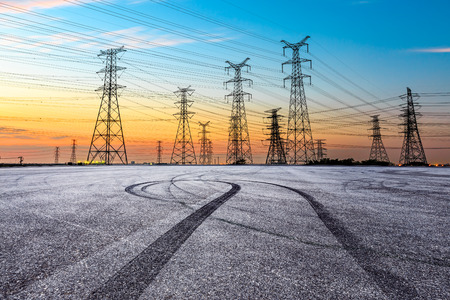 Asphalt road pavement and high voltage power lines at sunset
