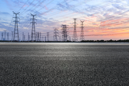 Asphalt road and high voltage power towers at sunset