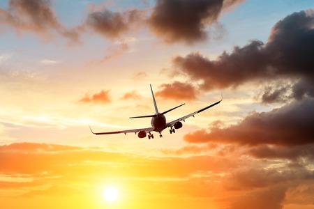 Kommerzielles Flugzeug, das während des Sonnenuntergangs über dramatische Wolken fliegt