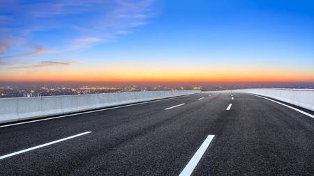 Empty asphalt road and modern city skyline at night Imagens