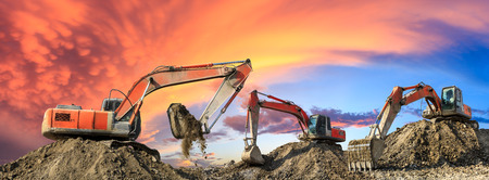 Three excavators work on construction site at sunset,panoramic view Banco de Imagens