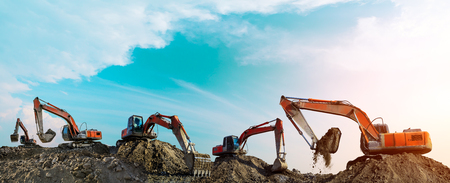 Many excavators work on construction site at sunset,panoramic view Stockfoto