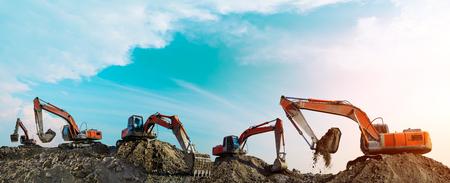 Muchas excavadoras trabajan en el sitio de construcción al atardecer, vista panorámica Foto de archivo