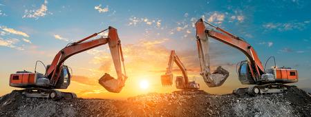 Drie graafmachines werken op de bouwplaats bij zonsondergang, panoramisch uitzicht Stockfoto
